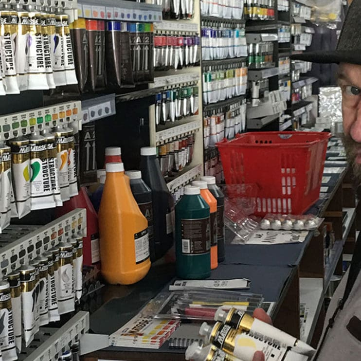 Man with hat on putting away paints at art shop