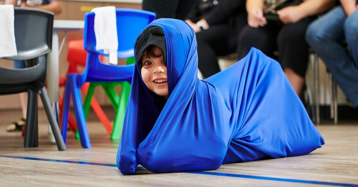 boy plays in a large piece of cloth