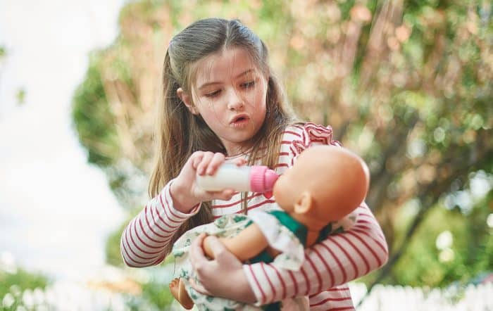 Positive effects of pretend play - girl plays with doll