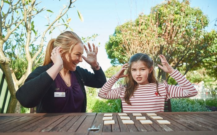 therapist and child playing a game outside