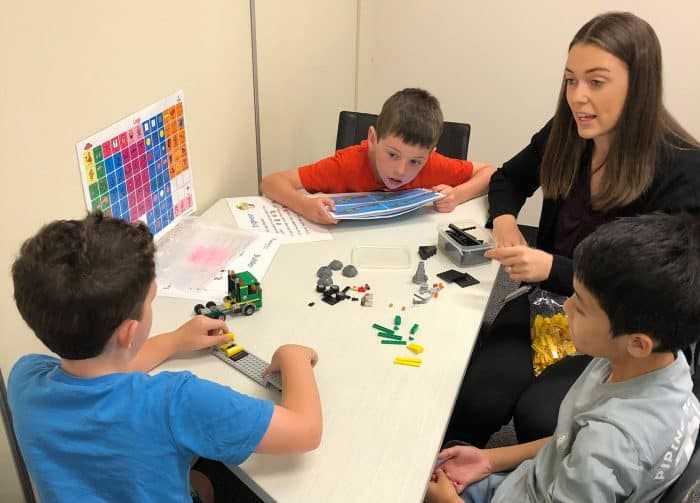 Three boys doing LEGO Therapy with a therapist