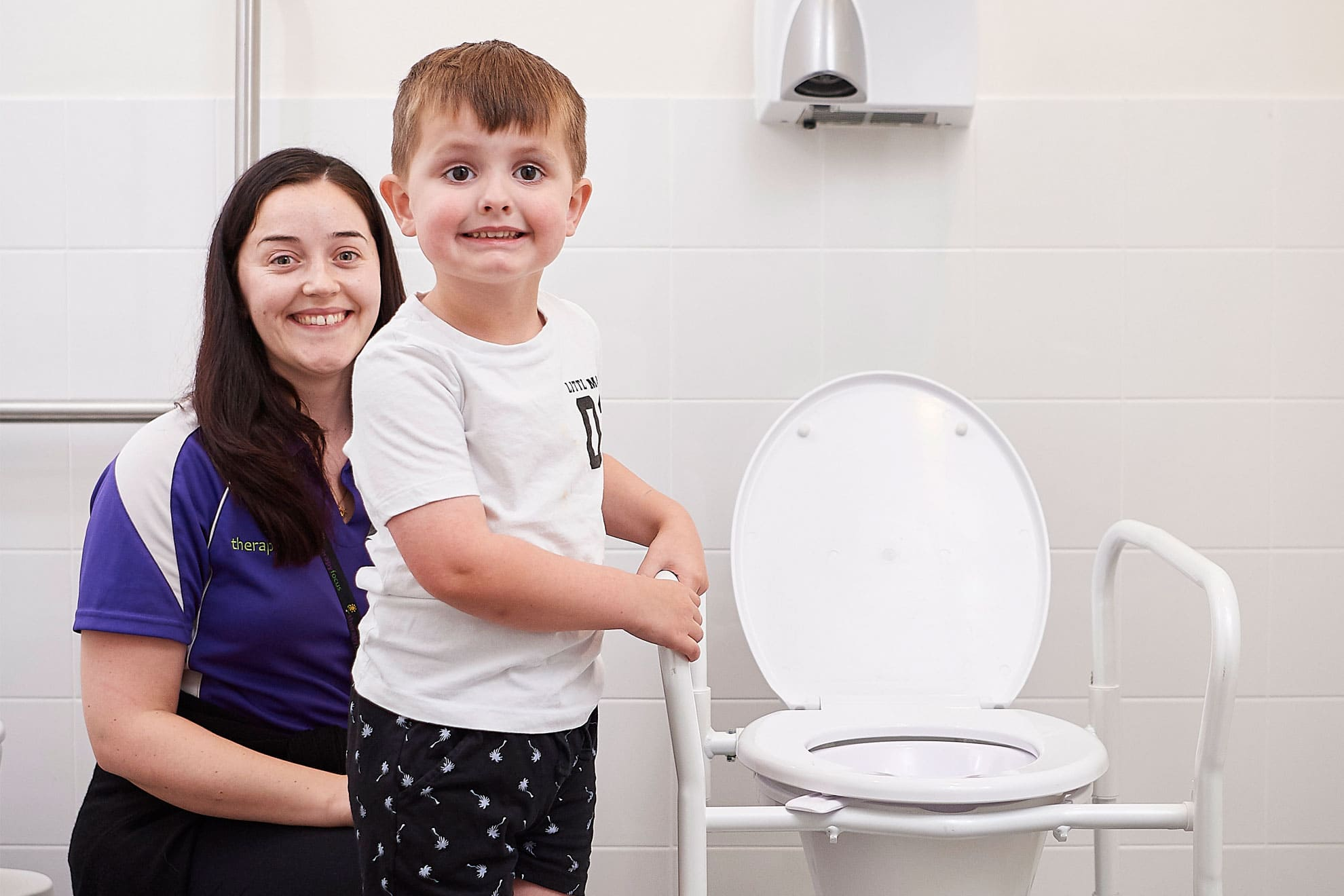 A boy and therapist standing next to a toilet