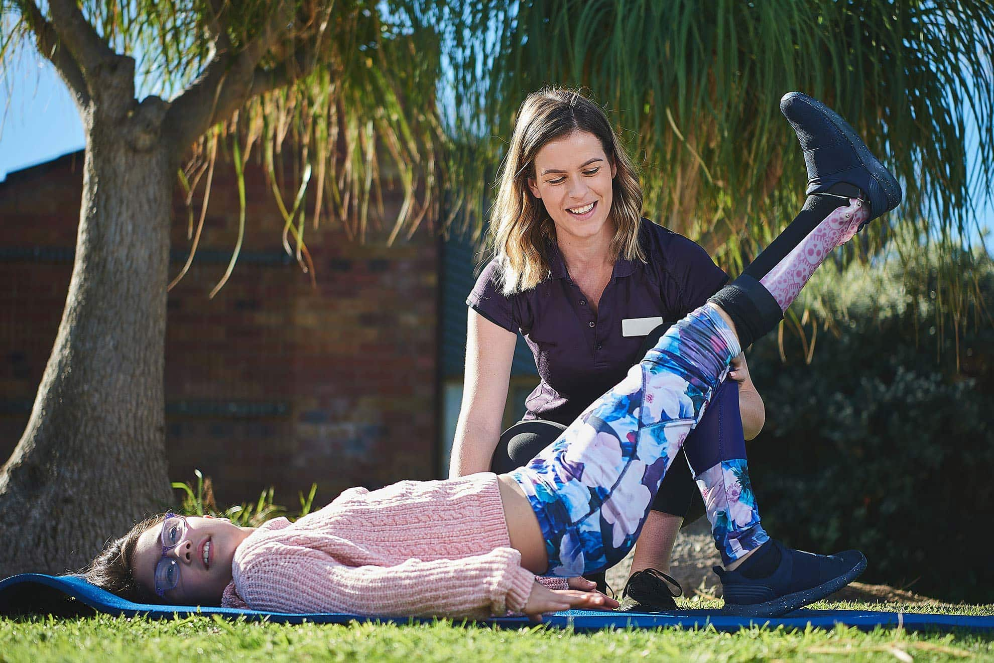 A physiotherapist helping a girl do an exercise