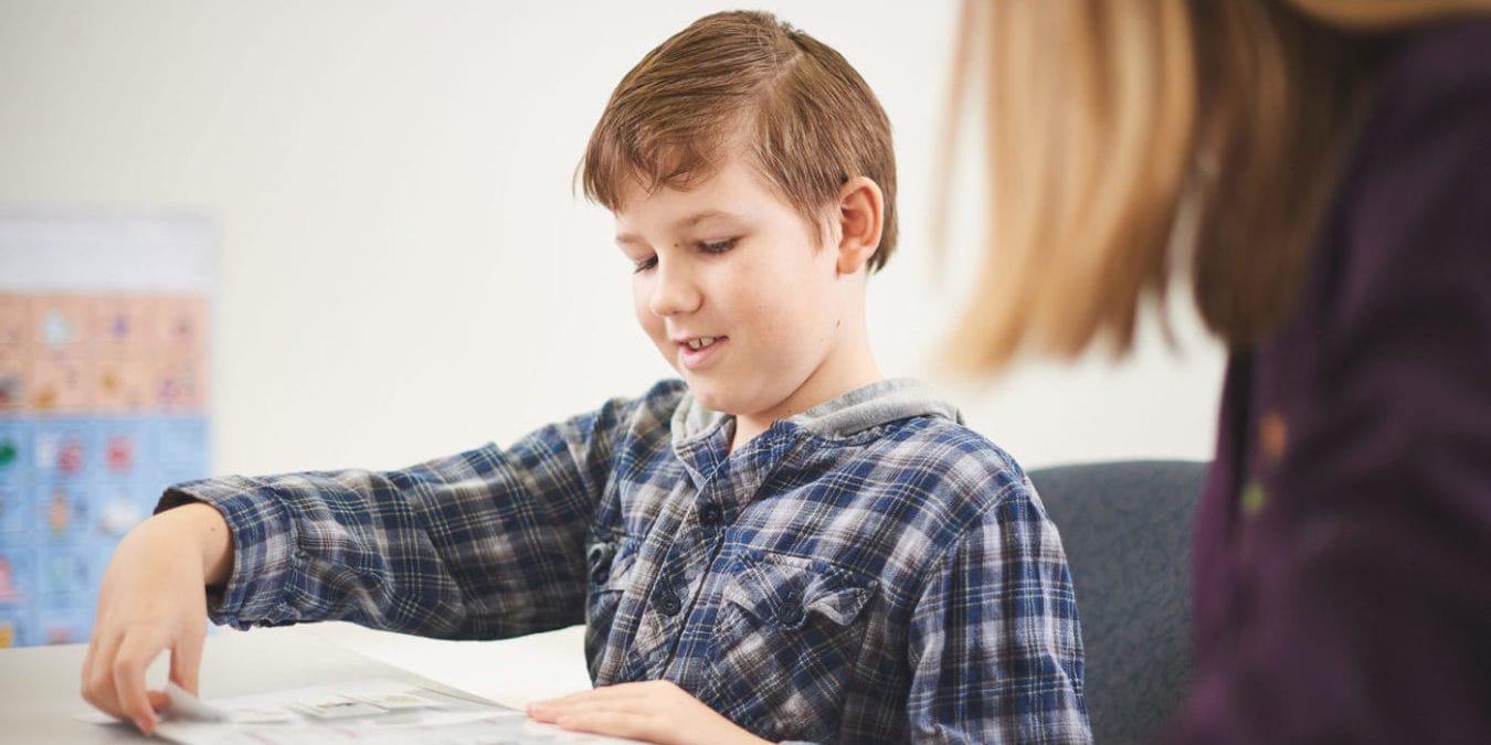A boy placing symbols on a chart during a speech pathology session