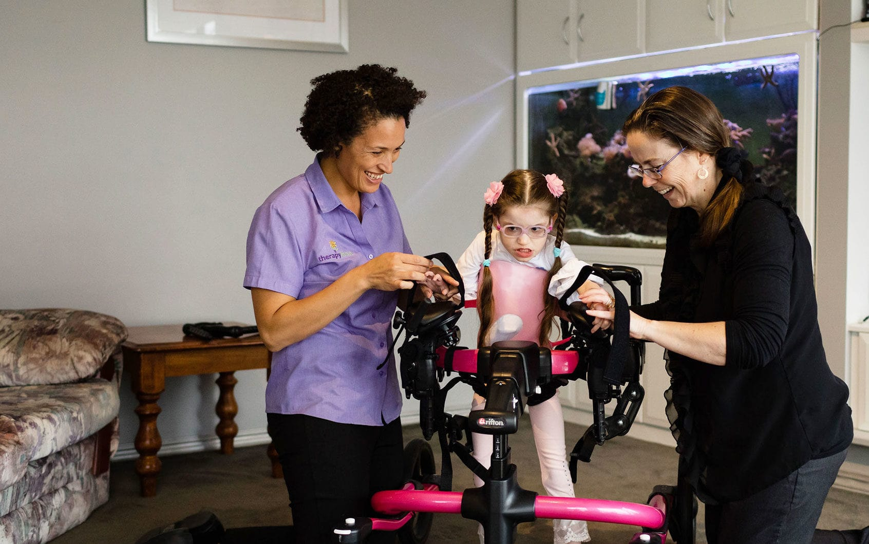 A young girl in a walker with her Mum and therapist