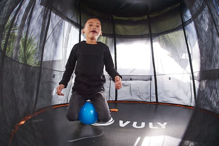A young boy jumps on a trampoline.