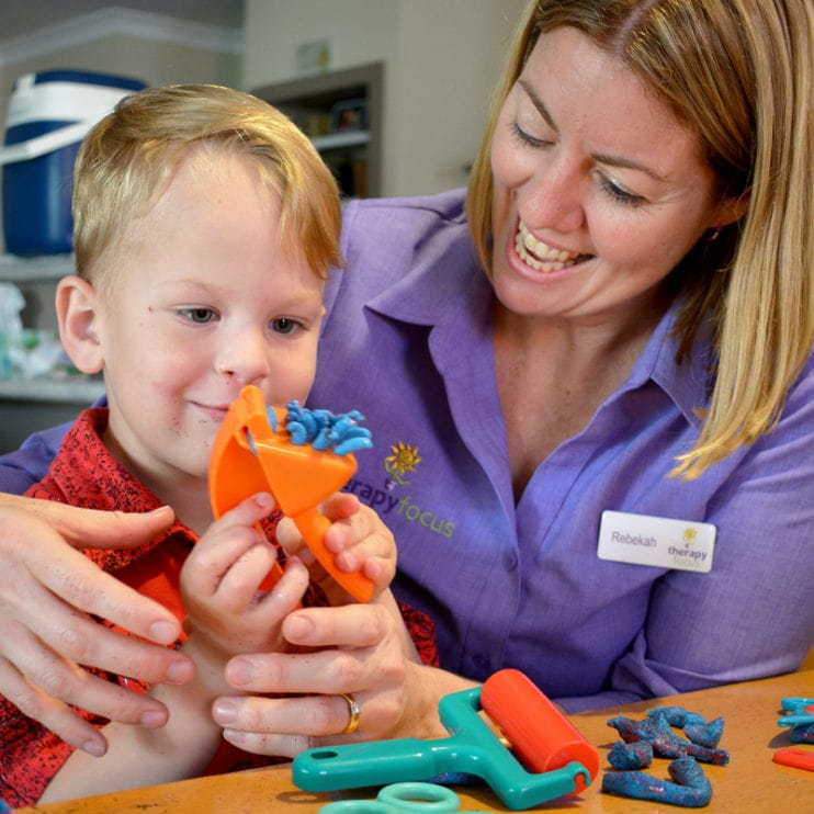 Cody and his therapist sit together and interact with some sensory toys.