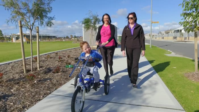 Theodore rides his bike and is accompanied by mum Sharon and his therapist. They are moving through a park on a pathway.